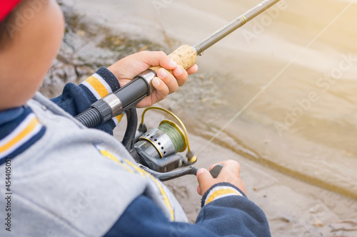 A boy is fishing with a rod on a summer day on the river. Fototapet