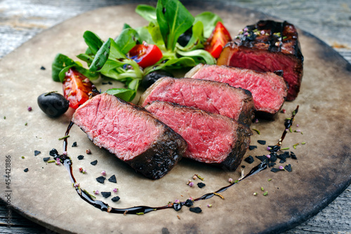 Rustic style barbecue dry aged wagyu roast beef steak with lambs lettuce and tom Fototapet