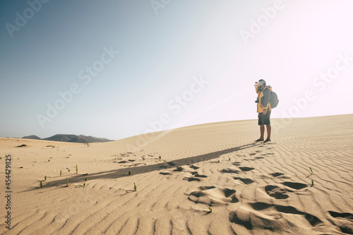 Photographie One man standing on the sand desert dunes with backpack looking far - climate ch