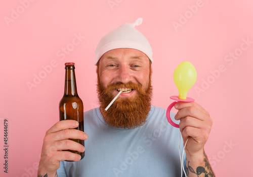 Foto Happy man with beard and tattoos acts like a little newborn baby with beer in ha
