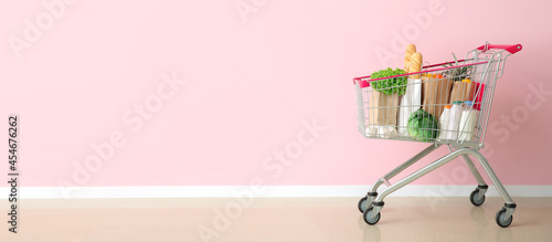 Foto Shopping cart with products near color wall with space for text