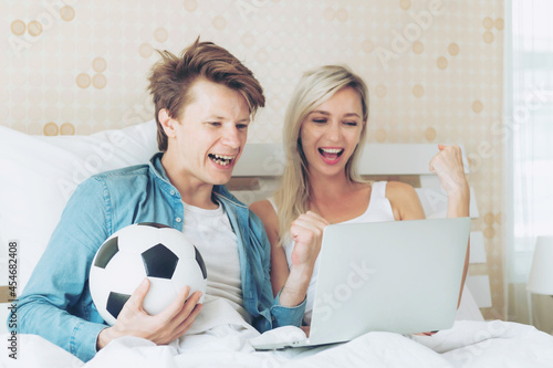 Canvas Print Young couple handsome husband and beautiful wife feel great when the soccer they