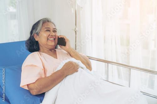 Fotografia Elderly patients in hospital bed patients using smart phone call to descendant r