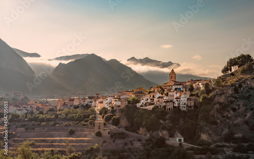 Fotografia View of the village of Polop, Spain at sunrise with the mountains in the clouds in the background