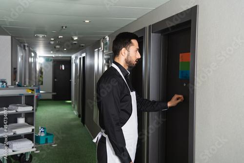 side view of bearded housekeeper knocking door in hotel room Fototapete