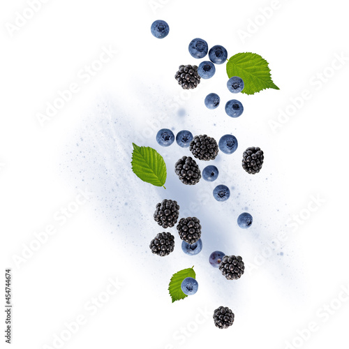 Photo Fresh blueberries and blackberries dewberries and with leaves flying falling