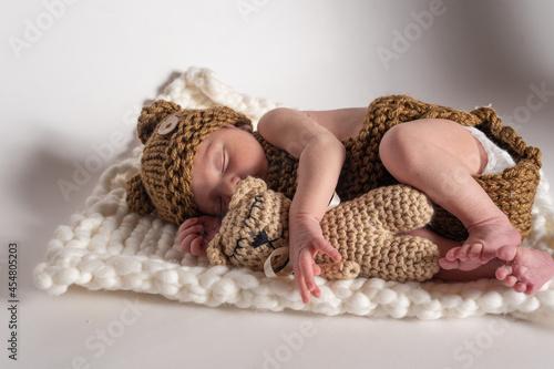 bebé recién nácido con osito de peluche Fototapet