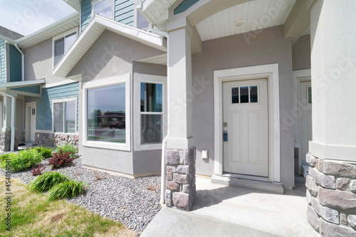 Fotografia Townhouse exterior with white front door and bay windows