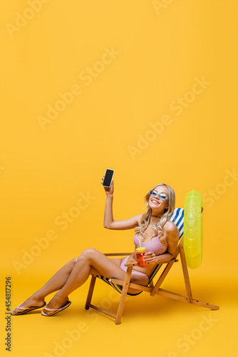 smiling woman in sunglasses and swimsuit sitting in deck chair with cocktail and smartphone on yellow Fototapet