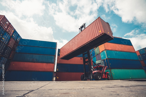 Cargo container for overseas shipping in shipyard with heavy machine . Logistics supply chain management and international goods export concept .