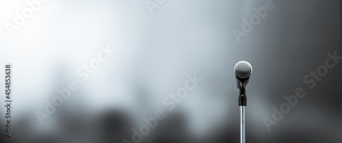 Fotografiet Microphone Public speaking background, Close-up the microphone on stand for speaker speech presentation stage performance with blur and bokeh light background