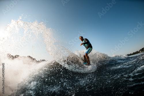 view of the splashing wave along which man rides on wakesurf on the background o Fototapeta