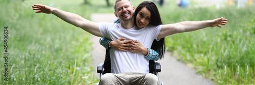 Woman hugs joyful man in wheelchair in park Fototapet