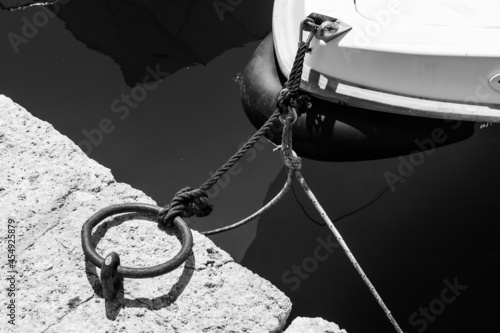 Tablou Canvas Grayscale shot of an anchored boat on a concrete dock