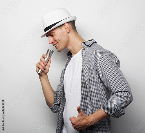 Canvas Print Lifestyle, people and leasure concept: a young man wearing a grey shirt and hat holding a microphone and singing