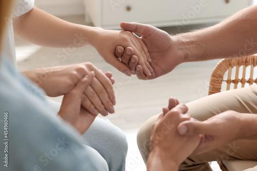 Billede på lærred Group of religious people holding hands and praying together indoors, closeup