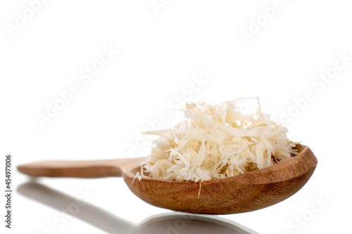 Canvastavla Grated horseradish root with a wooden spoon, close-up, isolated on white