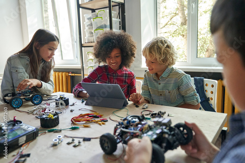 Multiethnic school kids students making robotic cars using tablet computer. Diverse junior children pupils building robot vehicle learning at table at STEM code ai engineering science education class.