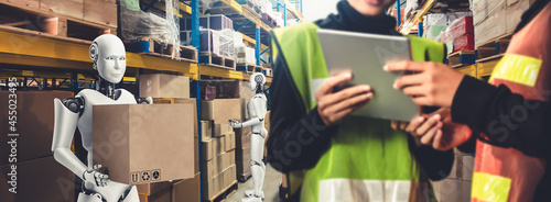Fotografia Innovative industry robot working in warehouse together with human worker