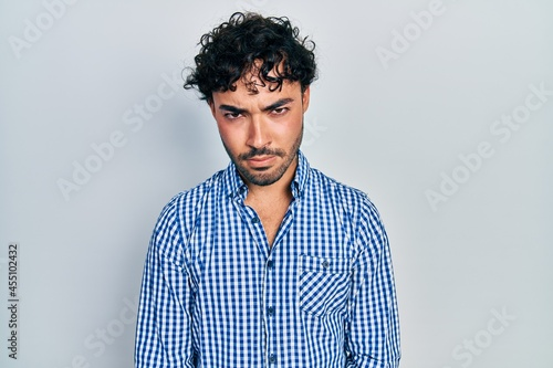 Fototapeta Young hispanic man wearing casual clothes skeptic and nervous, frowning upset because of problem