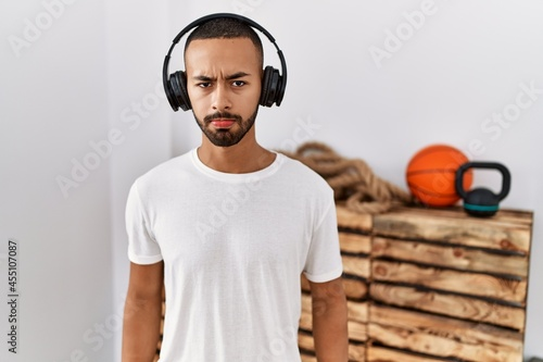 Obraz na plátně African american man listening to music using headphones at the gym skeptic and nervous, frowning upset because of problem