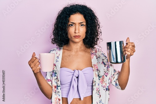Obraz na plátně Young latin girl holding cup of coffee and jar of milk skeptic and nervous, frowning upset because of problem