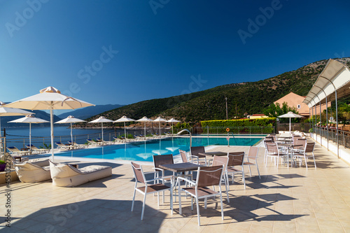 Canvastavla Luxury swimming pool with empty deck chairs, tables and umbrellas at the resort with beautiful sea view
