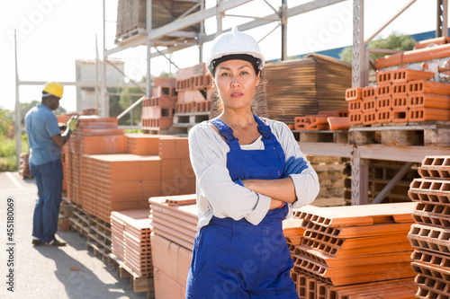 Fotografie, Obraz Portrait of female worker at warehouse of building materials in the open air