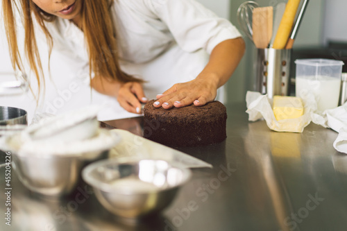 Fototapeta Confectioner girl is preparing a cake biscuit with white cream and chocolate