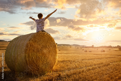 Canvastavla Boy sitting on a hay bale with arms raised in summer watching the sunset