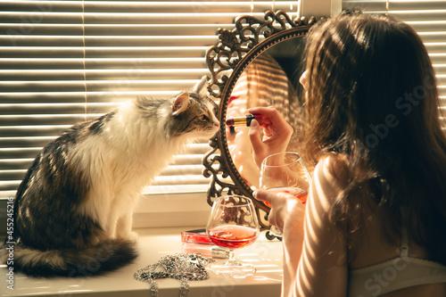 Fotografia Beautiful Young Woman With Her Cat Applying Cosmetics Near Mirror In Sun Light