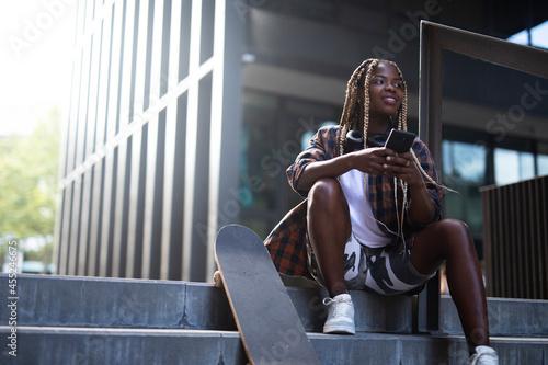 Slika na platnu Beautiful african-american woman with skateboard