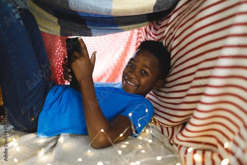 Fototapeta Portrait of happy african american boy sitting in blanket fort, using tablet