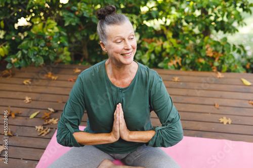 Happy senior caucasian woman practicing yoga, meditating in sunny garden