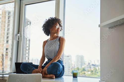 Fotografija Cute tranquil woman leaned back against the window looking away