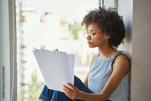 Slika na platnu Young serious beautiful curly-headed female with documents