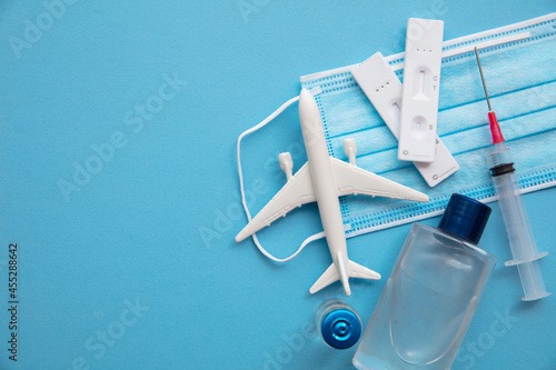 Covid air travel background. Airplane with a coronavirus protective face mask vaccine needle and test