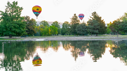Fotografiet Pair of hot air balloon float over the trees of a Boise City park