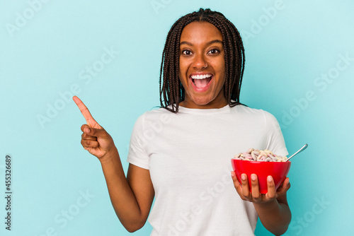 Canvas Young African American woman holding a bowl of cereales isolated on blue background  smiling and pointing aside, showing something at blank space
