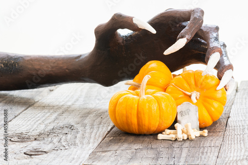 Fotografija Halloween concept with miniature pumpkins, tombstone, dog bones candy and bony h
