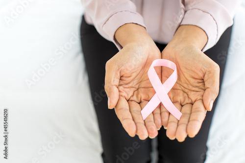 Photo Pink ribbon, on aged hand of illness woman, representing international fabric sy