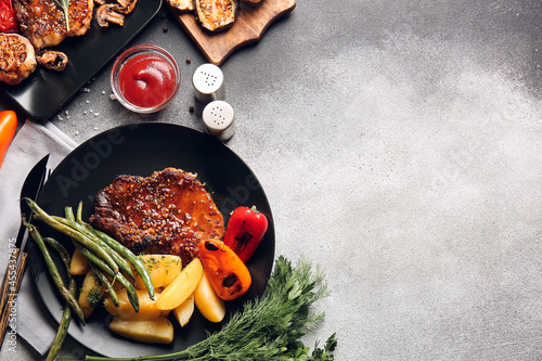 Stampa su Tela Plates with tasty pork steaks and grilled vegetables on grey background