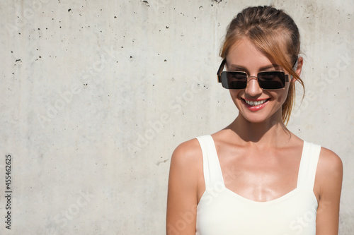 Beautiful woman with sunglasses outdoors on sunny day, space for text