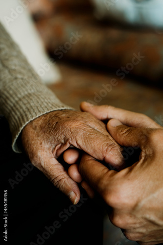 Tableau sur Toile young man holds the hand of an old woman