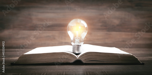 Fotografiet Light bulb and book. Knowledge and wisdom