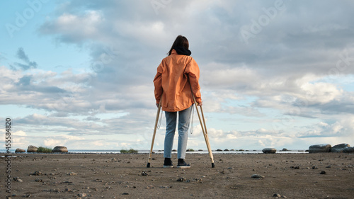 Billede på lærred A woman on crutches walks along the shore of the lake.