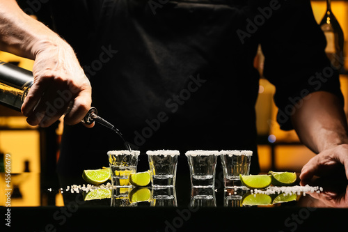 Fototapeta Bartender pouring tasty tequila into glasses at table in bar