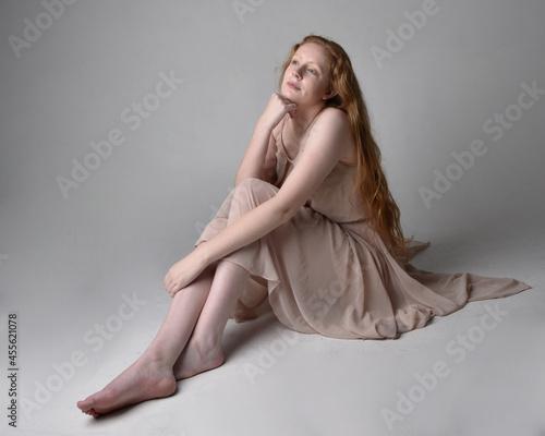 Fotografia Full length portrait of pretty red haired woman dancer,  wearing skin toned flowing fairy dress