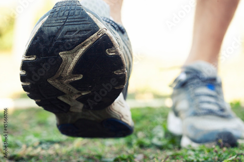 Fototapeta premium Closeup view of runner's shoes running throug the countryside