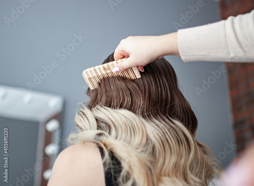 Fototapeta stylist hairdresser makes a hairstyle for a girl in his beauty salon, hollywood